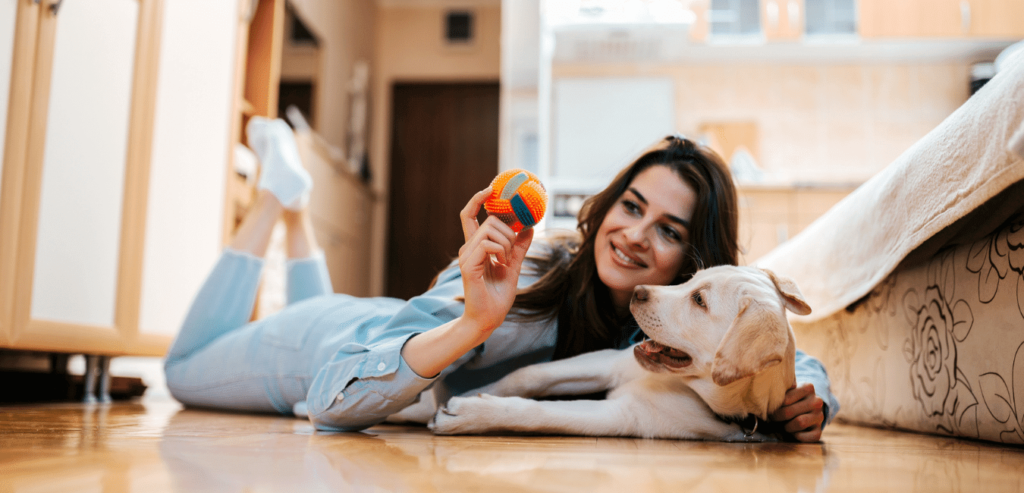 Woman playing on floor with dog at woodsview