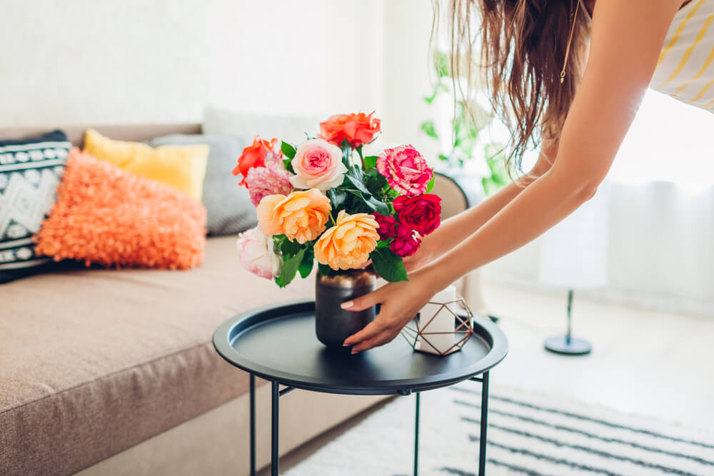 Woman putting flowers on the coffee table